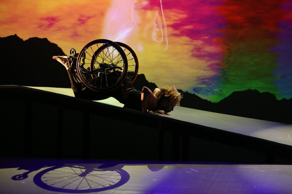 Andromeda slides in a spider position on her stomach down the shiny ramp. The shadow of her wheelchair is visible; her curly hair glows. Photo by MANCC / Chris Cameron.